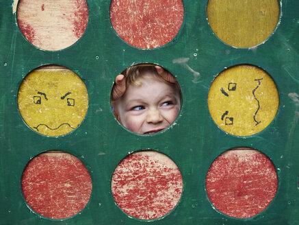 Portrait of little boy hiding on playground - MUF01538