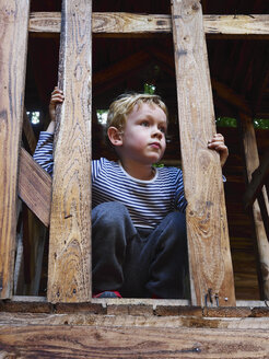 Portrait of littleboy crouching on climbing frame - MUF01547