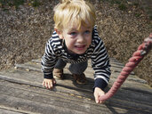 Portrait of little boy on climbing frame - MUF01550