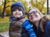 Portrait of mother and little son in an autumnal park - MUF01553