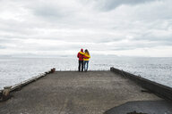 Iceland, North of Iceland, back view of couple standing on jetty looking at view - AFVF00599