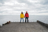Iceland, North of Iceland, young couple standing hand in hand on jetty - AFVF00602