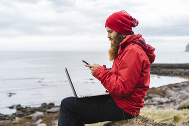 Iceland, North of Iceland, man with laptop sitting near the sea using cell phone - AFVF00605