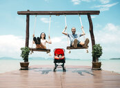 Thailand, Koh Lanta, happy parents  on wooden swings in front of the sea and sleeping baby in a stroller - GEMF02047