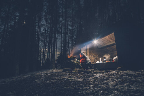 Sweden, Sodermanland, man at shelter with campfire at night - GUSF00911
