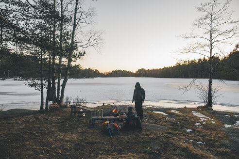 Sweden, Sodermanland, backpacker resting at a remote lake in winter - GUSF00923