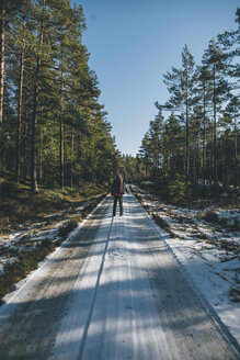 Sweden, Sodermanland, backpacker standing on path in remote forest in winter - GUSF00932