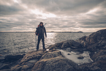 Sweden, Sodermanland, backpacker standing at the seashore under cloudy sky - GUSF00938