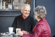 Senior couple at sidewalk cafe drinking coffee and chatting - CUF20286