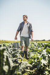 Man in vegetable garden carrying watering can, looking away - CUF20301