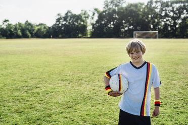 Boy wearing German soccer shirt, holding football - MJF02308