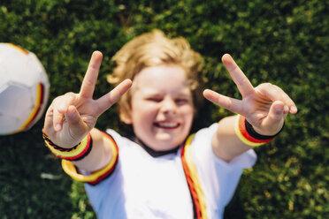 Boy in German soccer shirt lying on grass, making victory sign - MJF02311
