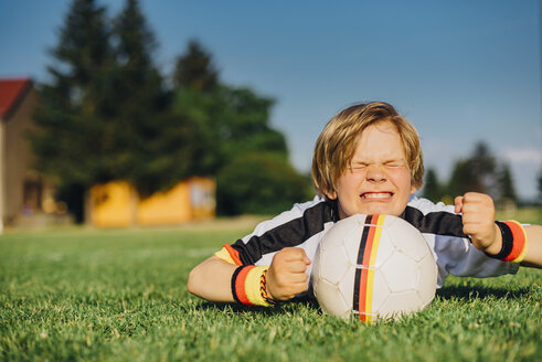 Boy in German soccer shirt lying on grass, keeping fingers crossed for world championship - MJF02314