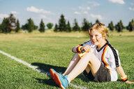 Boy wearing German soccer shirt, blowing horns on soccer field - MJF02317
