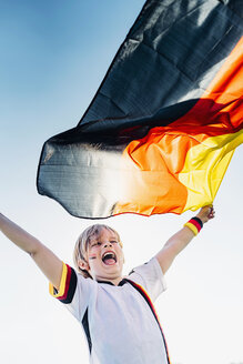 Boy, enthusiastic for soccer world championship, waving German flag - MJF02323