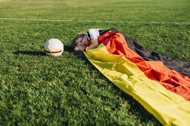 Boy sleeping on soccer field, covered iwith German flag - MJF02326