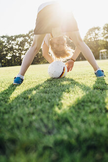 Boy on soccer field, bending over, looking through his legs - MJF02338