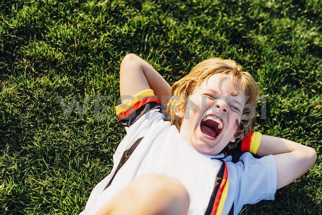 Boy in German soccer shirt lying on grass, laughimg - MJF02341 - Jana Mänz/Westend61