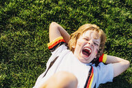 Boy in German soccer shirt lying on grass, laughimg - MJF02341