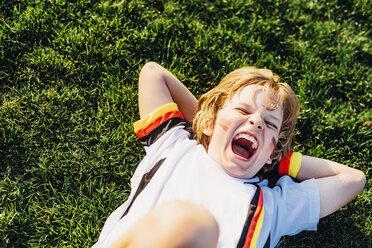 Boy in German soccer shirt lying on grass, laughimg - MJF02341
