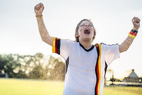 Boy wearing German soccer shirt screaming for joy, standing in water splashes - MJF02347