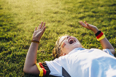 Boy in German soccer shirt lying on grass, laughing and screaming - MJF02350