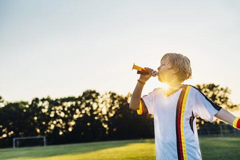 Boy wearing German soccer shirt, blowing horns on soccer field - MJF02353
