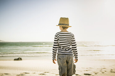 Young boy standing on beach, looking at sea, rear view - CUF20528