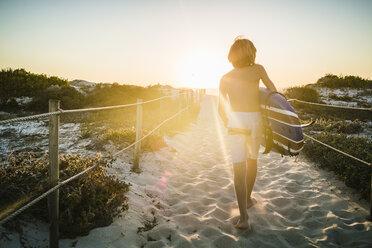 Young boy, walking along beach walkway, holding surfboard, rear view - CUF20537