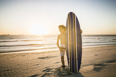 Portrait of young boy standing on beach, holding surfboard - CUF20540