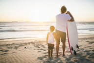 Father and son standing on beach,with surfboard, looking at ocean, rear view - CUF20543