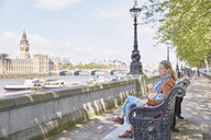 Mother and son resting on bench by river thames - CUF20570