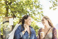 Two women friends with takeaway coffee chatting in park, Franschhoek, South Africa - CUF20618