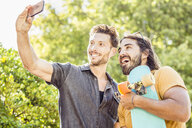 Man and skateboarder friend taking smartphone selfie in park, Franschhoek, South Africa - CUF20621