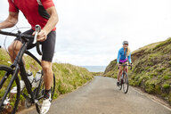 Cyclists riding on road overlooking ocean - CUF20873