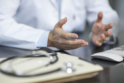 Files and stethoscope on desk in medical practice with doctor gesturing - ZEF15506