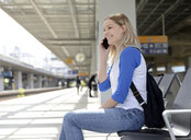 Young blond woman using smartphone at platform - BFRF01825