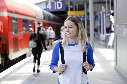 Portrait of blond woman with backpack on platform - BFRF01828