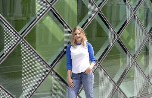 Blond young woman leaning on a glass facade - BFRF01834