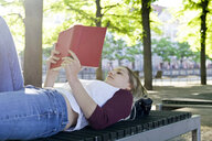 Young woman reading a book on bench - BFRF01840