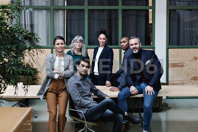 Portrait of confident business team at table in creative office - MASF07634
