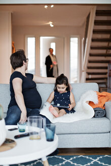 Mother sitting with daughter on sofa looking at woman entering house - MASF07730