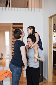 Smiling family enjoying while standing in living room at home - MASF07733