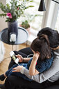 High angle view of mother and daughter wearing headphones while using mobile phone in living room - MASF07745