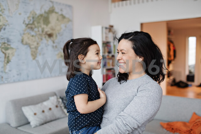 Smiling mother carrying daughter while standing at home - MASF07751