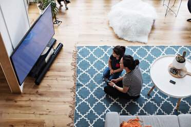 High angle view of mother and daughter watching television while sitting on floor at home - MASF07766
