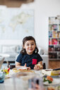 Portrait of cute smiling girl having breakfast at table in house - MASF07778