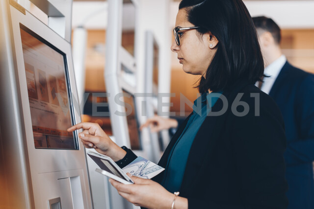 Side view of mid adult businesswoman using check in machine at airport - MASF07805 - Maskot/Westend61