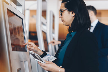 Side view of mid adult businesswoman using check in machine at airport - MASF07805