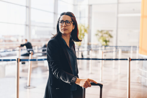 Mid adult businesswoman looking away in airport terminal - MASF07808